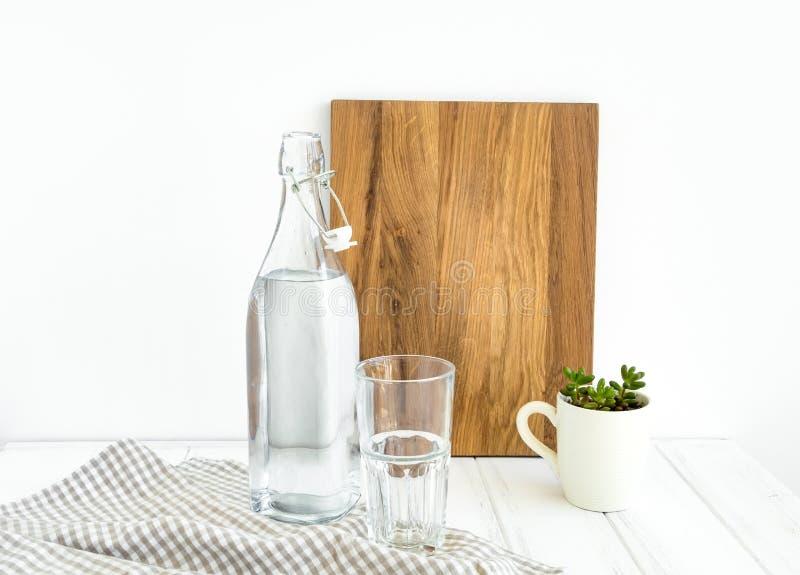 Tappningflaska av vatten, tomt exponeringsglas och en skärbräda på den vita tabellen, mot den vita väggen arkivfoto