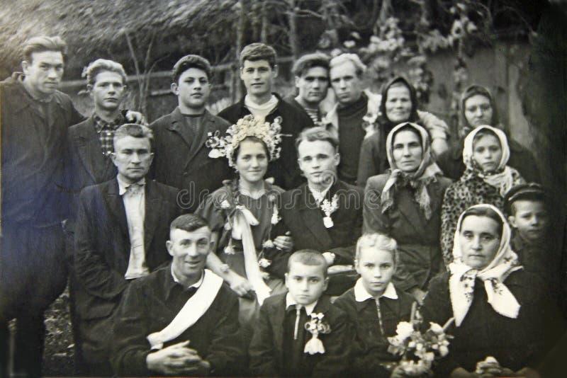 Tappningfoto av brudgummen, bruden och gäster Ukrainskt bröllop circa 1960 royaltyfri foto