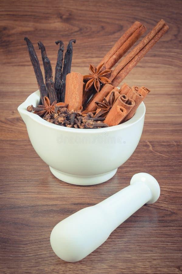 Tappningfoto, doftande anis-, kryddnejlika-, kanel- och vaniljpinnar i mortel royaltyfria foton