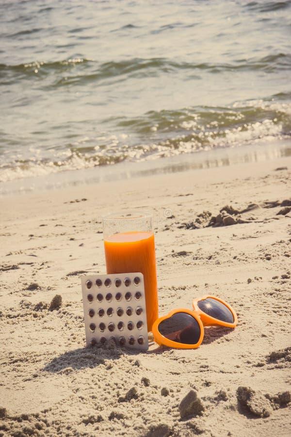 Tappningfoto, medicinska preventivpillerar, morotfruktsaft och solglasögon på stranden, vitamin A och härlig hållbar solbränna royaltyfria foton