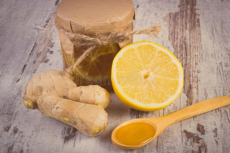 Tappningfoto, ny citron, honung och ingefära på trätabellen, sund näring arkivfoton
