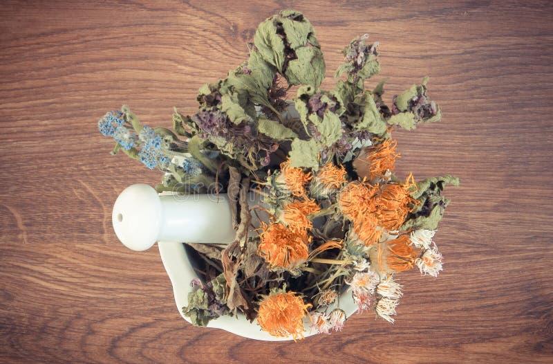 Tappningfoto, torkade örter och blommor i vit mortel, herbalism, garnering arkivbilder