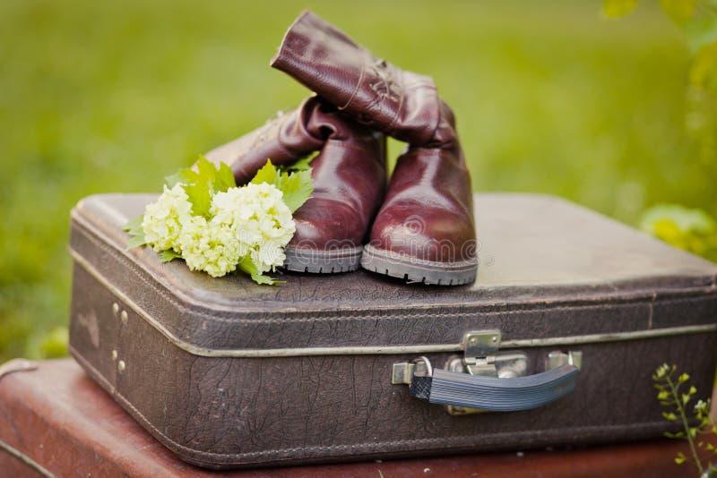 Tappninggarneringar: gamla kängor och resväskor med den blommande våren blommar royaltyfri fotografi