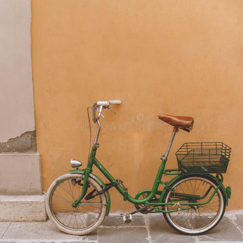 tappninggräsplancykel som står den near orange väggen, arkivfoto