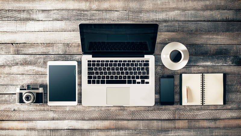 Tappninggrungeskrivbord med bärbara datorn fotografering för bildbyråer