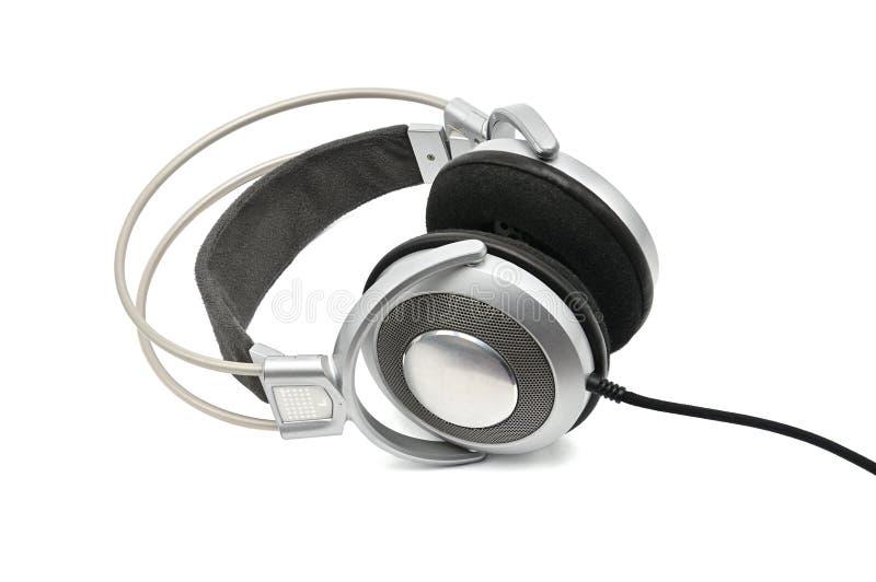 Tappninghörlurar för att lyssna som låter, och musik på en vit bakgrund arkivbilder
