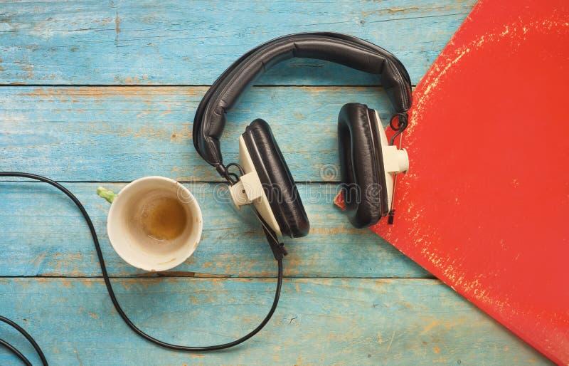 Tappningheadphone, vinylrekord, kopp kaffe som lyssnar till musik, åtlöje upp, utrymme för fri kopia royaltyfria foton