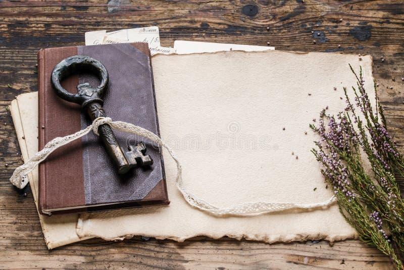 Tappningjärntangent, gammal bok och hemlighetbokstäver royaltyfri fotografi
