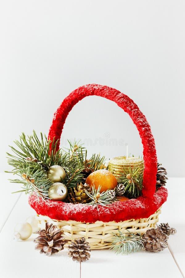 Tappningjul eller xmas-sammansättning korgen med tangerin, sörjer kotten, guld- bollar, granfilialer och stearinljuset arkivfoton