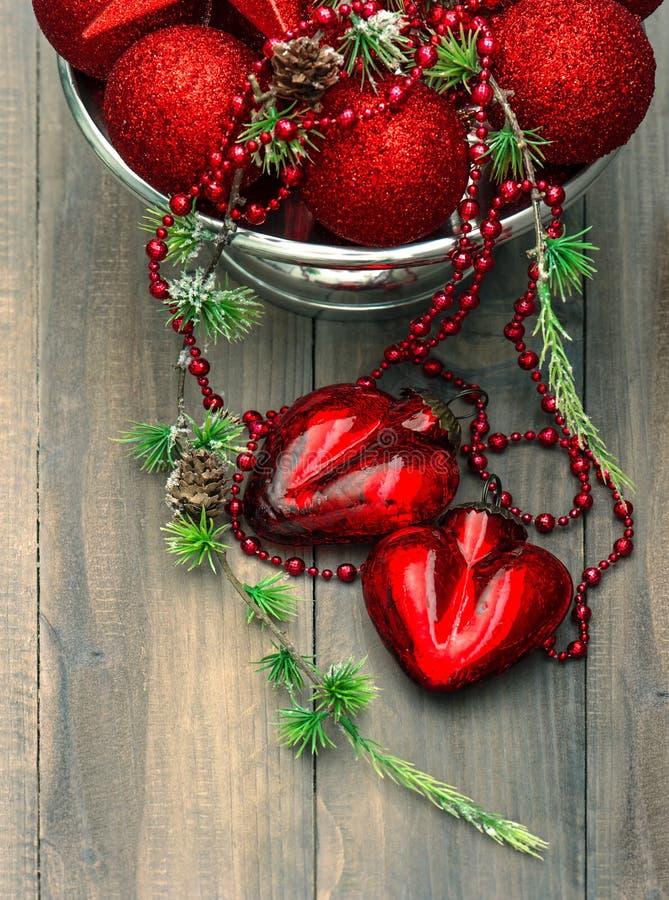 Tappningjulbakgrund med röda struntsaker och hjärtor royaltyfria bilder