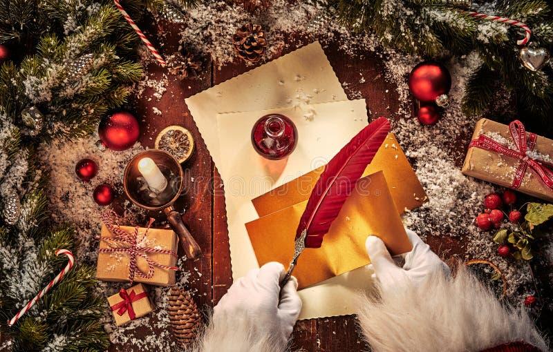 Tappningjulplats med Santa Claus som skriver ett brev med en fjäderfjäderpenna och garneringar på en lantlig tabell med royaltyfri fotografi