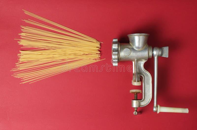 Tappningköttkvarn och pasta på röd bakgrund, bästa sikt, minimalism royaltyfria foton