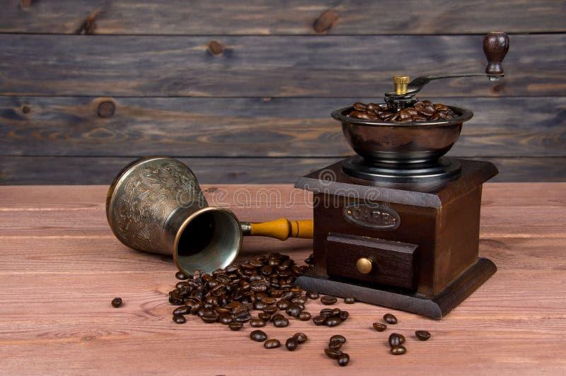 Tappningkaffekvarn, turkkopparkaffekruka och kaffebönor på brun träbakgrund arkivbild