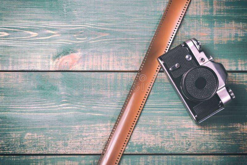 Tappningkamera med filmen på grön träbakgrund Tonat bild och fritt utrymme royaltyfri foto