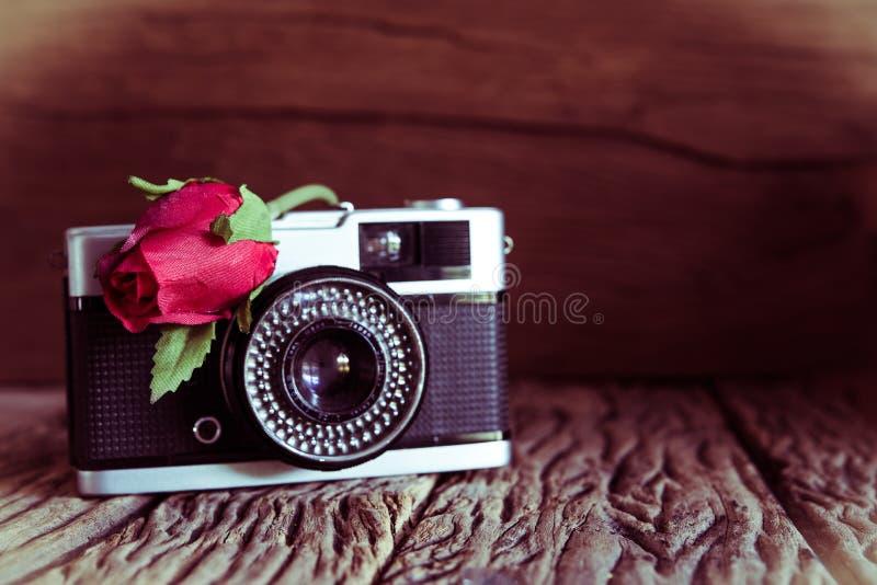 Tappningkamera med rosor på gammal wood bakgrund arkivfoto