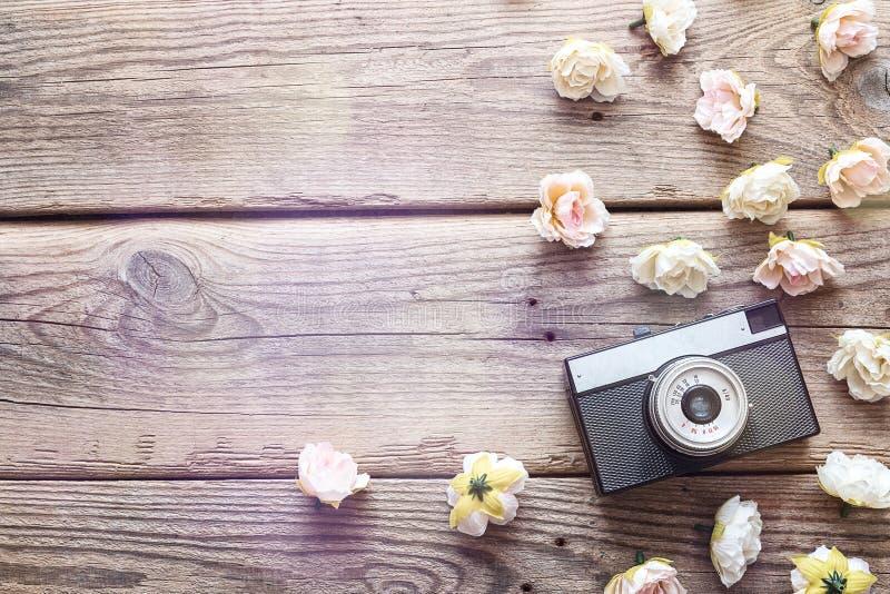 Tappningkameran med rosor blommar på gammal träbakgrund överkant royaltyfri fotografi
