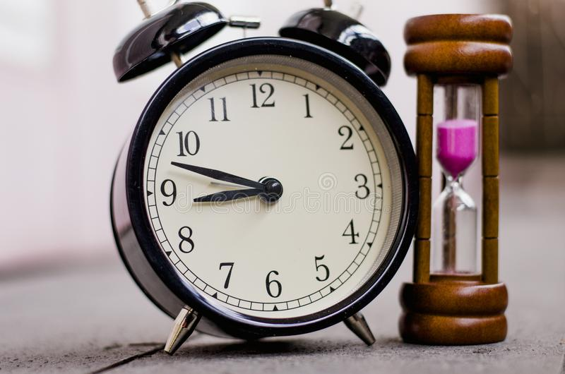 Tappningklocka och timglas eller sand-exponeringsglas för begrepp för tidledning arkivfoton