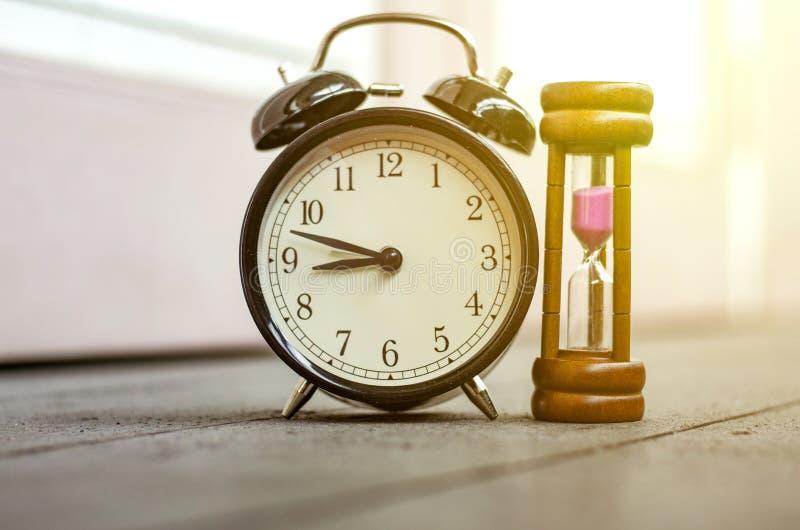 Tappningklocka och timglas eller sand-exponeringsglas för tidledning royaltyfri fotografi