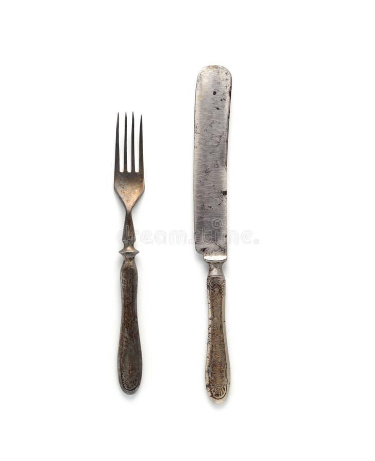 Tappningkniv och gaffel med den original- designen på handtagen på en vit bakgrund arkivfoton