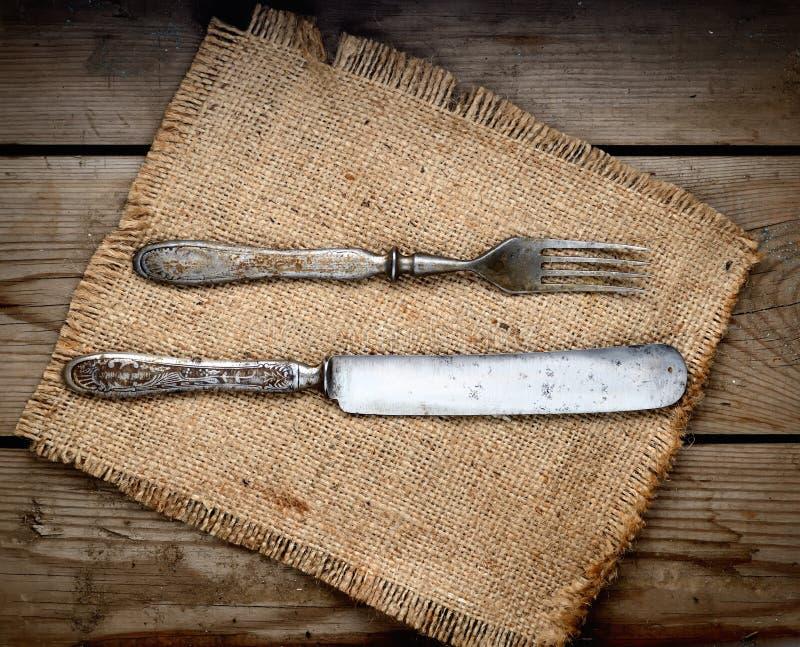 Tappningkniv och gaffel på en servett på en mörk träbakgrund royaltyfria bilder