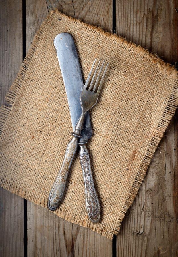 Tappningkniv och gaffel på en servett på en mörk träbakgrund arkivfoton