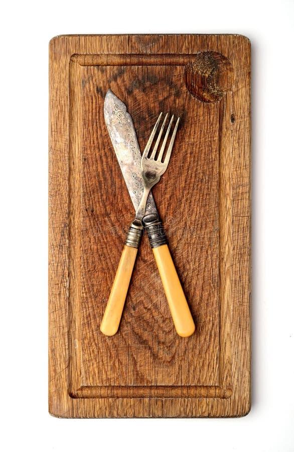 Tappningkniv och gaffel på en skärbräda på en vit bakgrund royaltyfri fotografi