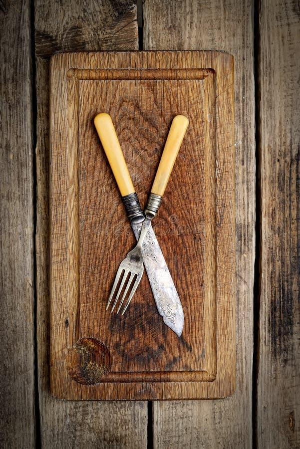 Tappningkniv och gaffel på en träbakgrund, bästa sikt royaltyfri fotografi