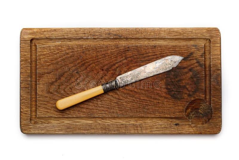 Tappningkniv på ett brunt bräde på en vit bakgrund arkivfoton