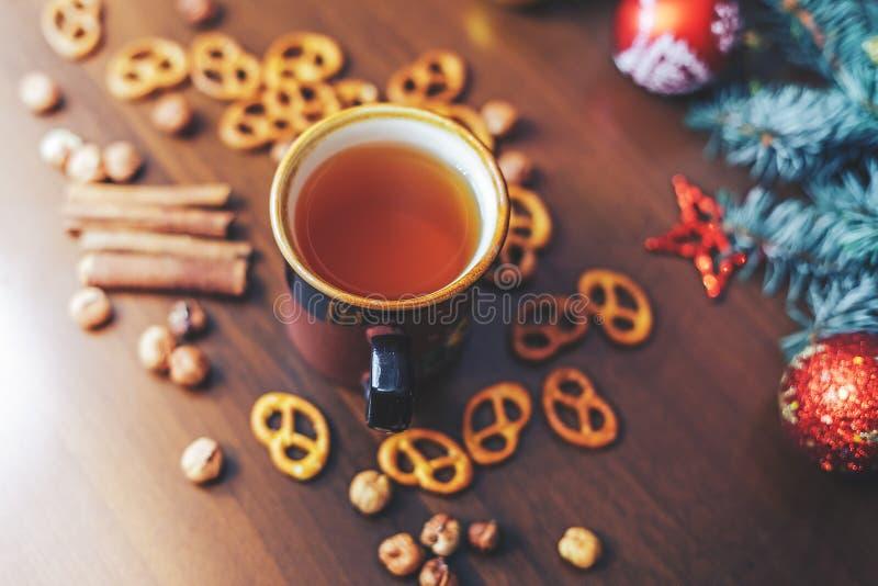 Tappningkopp av varmt te med smällare på dekorerad träbakgrund royaltyfria bilder