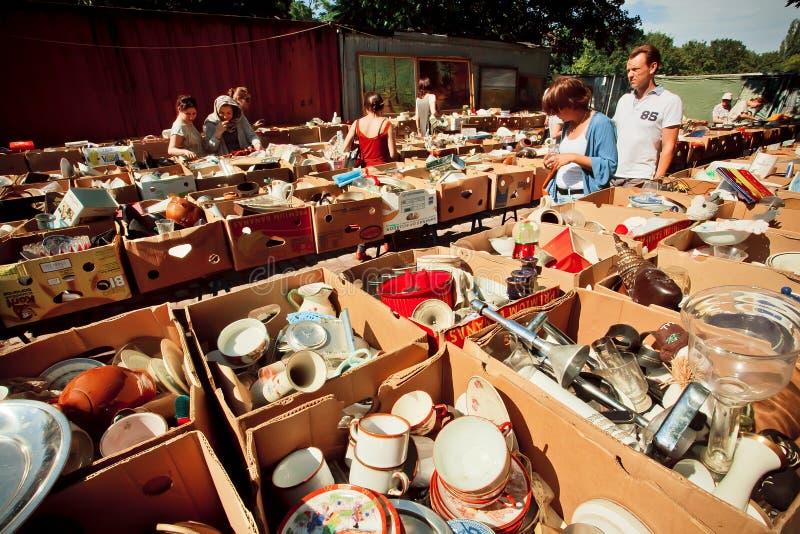 Tappningkoppar, plattor och folk som köper på loppmarknad arkivbild