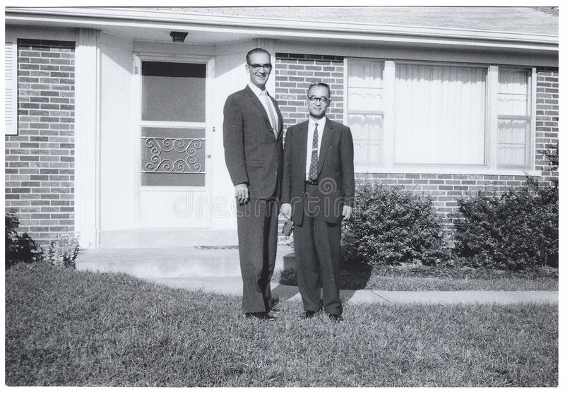 Tappningkort: Högväxt mankortslutningsman utanför surburban hus royaltyfri bild