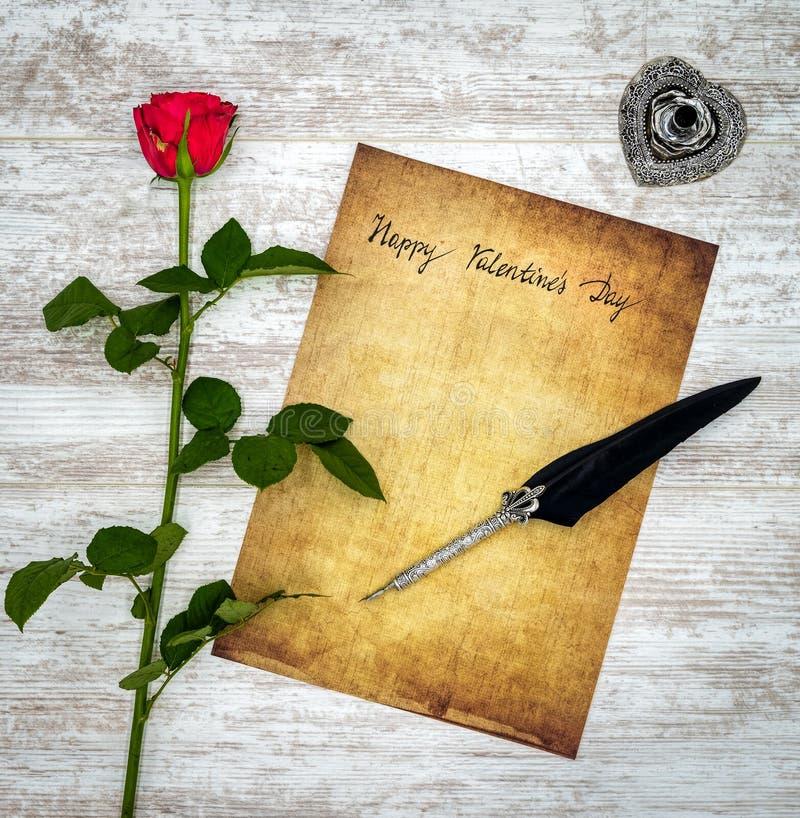 Tappningkort med den röda rosen, färgpulver och vingpennan på den vita målade eken - bästa sikt royaltyfria foton