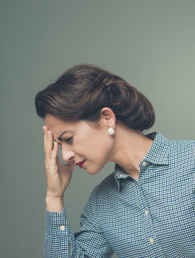 Tappningkvinna med huvudvärk royaltyfri foto