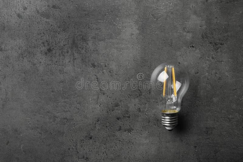 Tappninglampkulan på grå färger stenar yttersida Utrymme f?r text royaltyfria foton