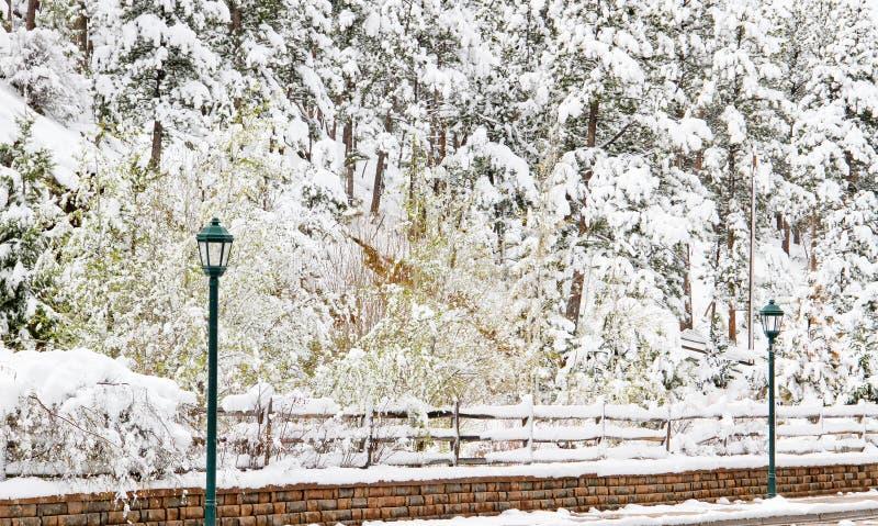 Tappningljusstolpar på snöig tegelstentrottoarkant royaltyfria foton