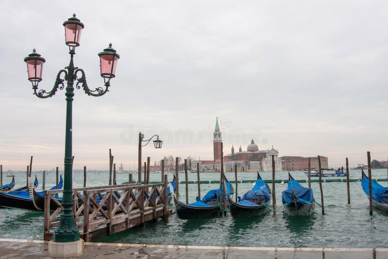 Tappninglyktstolpe med gondoler i den Venedig lagun i bakgrunden i Venedig, Italien royaltyfri bild