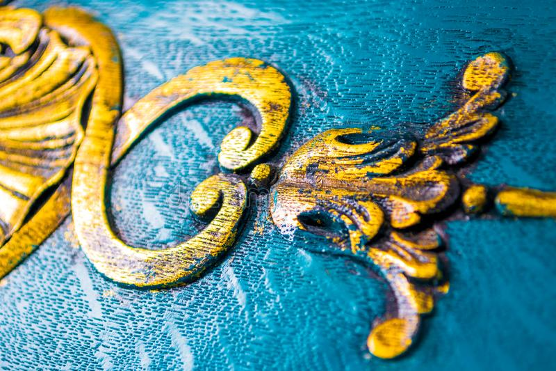 Tappningmöblemangdetaljer tätt upp Lyxiga blom- garneringar som snidas i trä som målas i ljus grungy guling arkivfoton