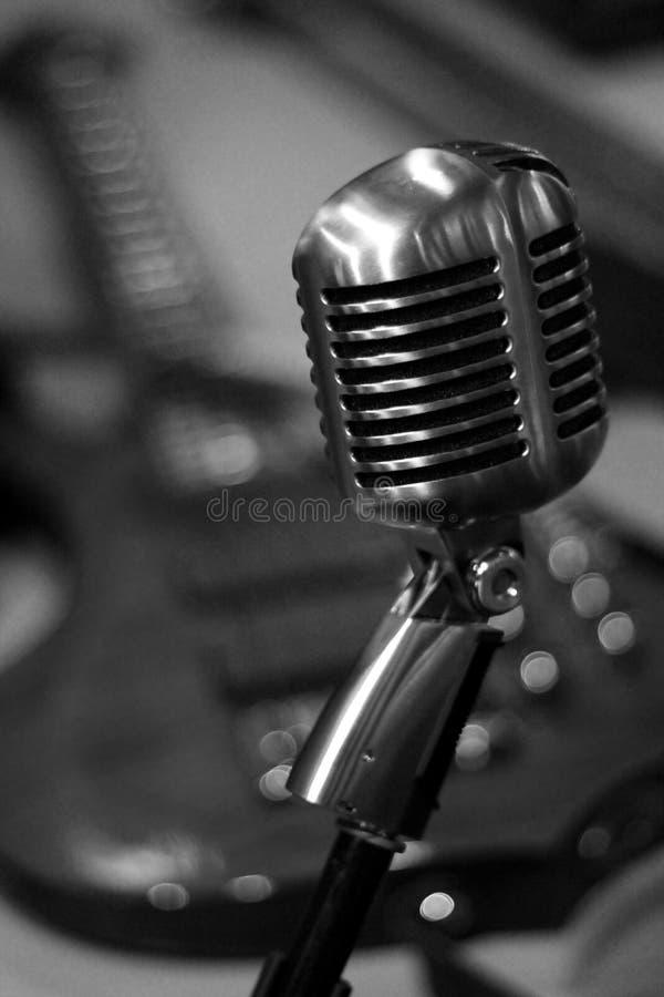 Tappningmikrofon med den elektriska gitarren i bakgrund som är svartvit royaltyfri foto