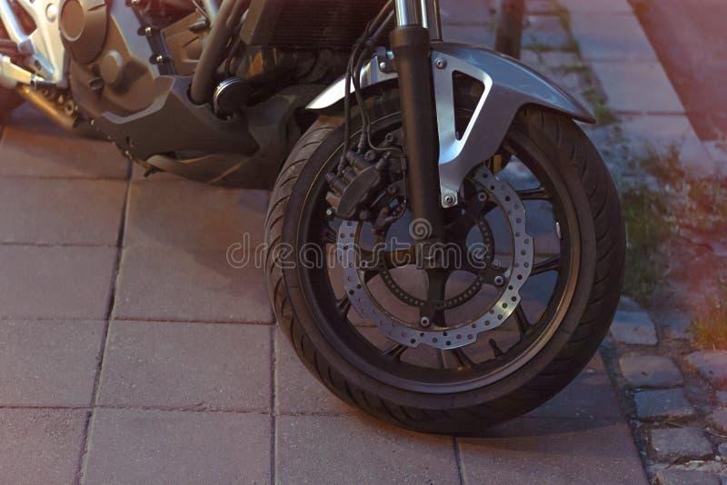 Tappningmotorcykel p? v?gen p? natten in mot stad royaltyfria foton