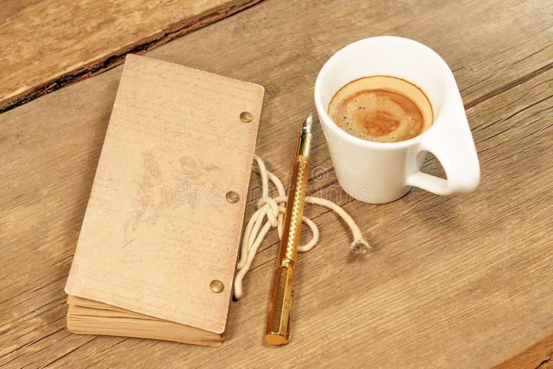 TappningNotepad, guld- reservoarpenna och kopp av espresso på trä royaltyfria foton