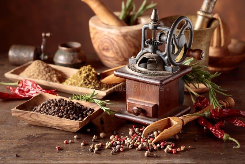 Tappningpeppar maler med k?ksger?d, kryddor och rosmarin p? en gammal tr?tabell arkivfoton