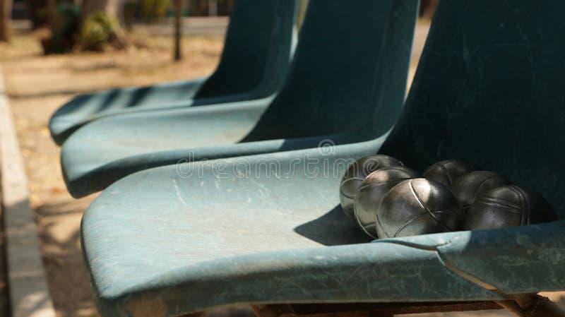 TappningPetanque bollar på gamla blåa ChairVintage Petanque bollar på gammal blåttstol royaltyfri foto