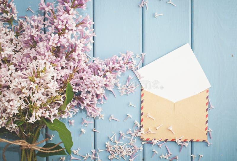 Tappningportokuvert med kortet och sommarbuketten av lilan arkivfoton