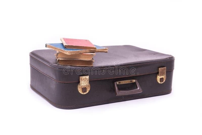 Tappningresväska med gamla böcker på vit isolerad bakgrund arkivbild