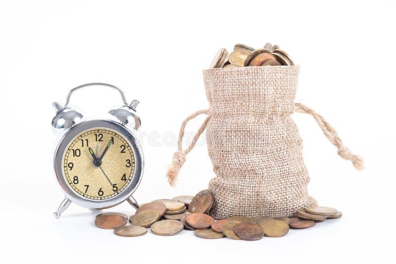 Tappningringklockaklocka med pengarpåsar och mynt på vit bakgrund Tid som ska investeras, prisvärd tid, familjeplanering, royaltyfria bilder