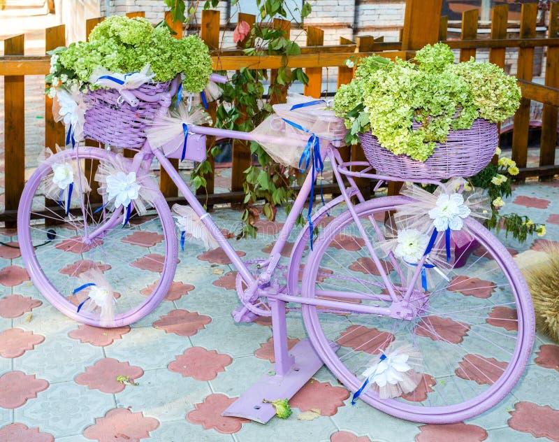 Tappningrosa färgcykel som dekoreras med gräsplanblommor och vitpilbågar arkivfoto