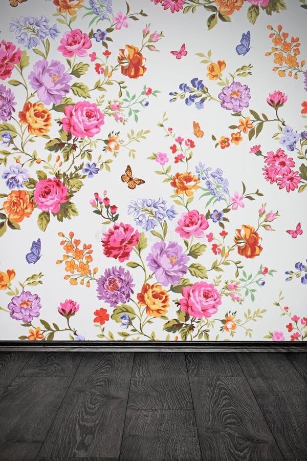 Tappningrum med den blom- färgrika tapeten och trägolvet royaltyfria foton