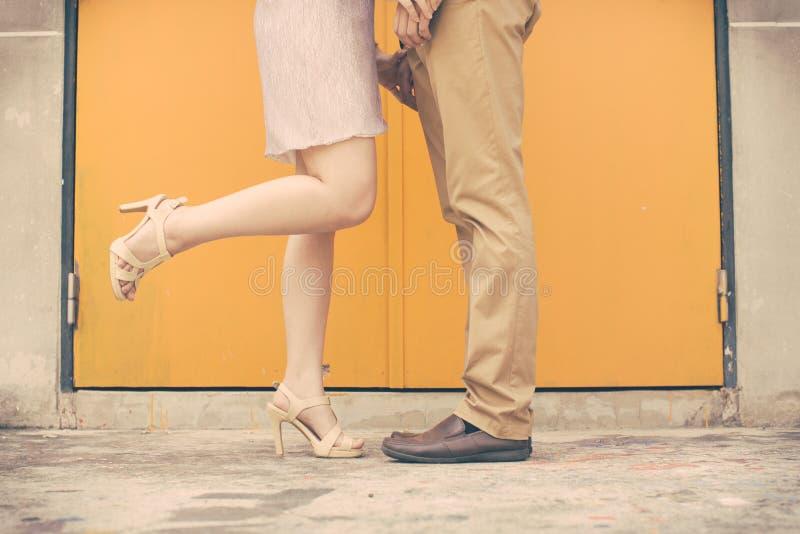 Tappningsignalen av mannen och kvinnlign lägger benen på ryggen under ett datum arkivfoto