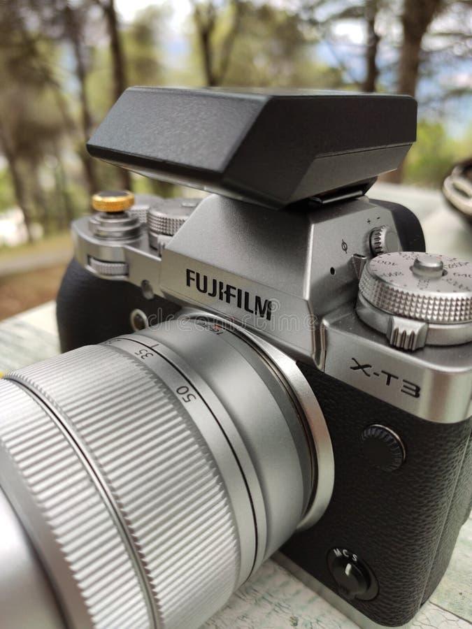 Tappningsilver och svart Fujifilm kamera med bruntläderremmen på trätabellen Kopiera utrymme f?r text arkivfoto