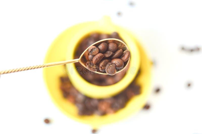 Tappningsked med bruna korn av kaffe i bakgrunden en gul kopp white f?r sked f?r bakgrundsb?nor kaffe isolerad arkivbild